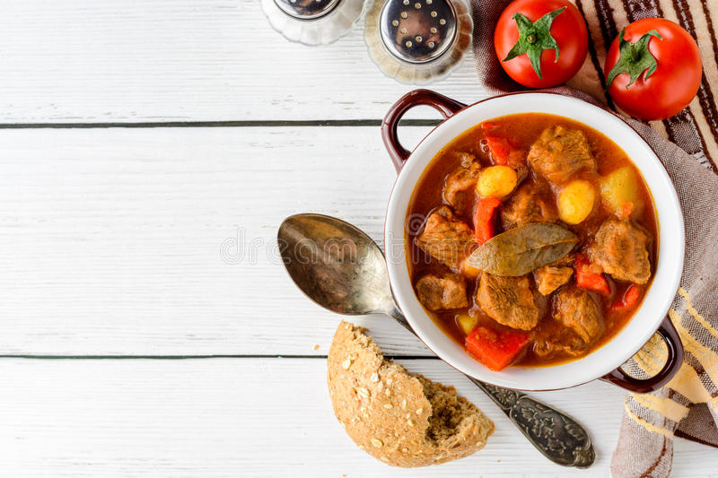 Goulash in ceramic bowl on white wooden background. Traditional hungarian soup. Rustic style. Top view royalty free stock photography