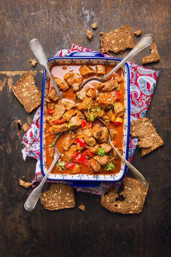 Goulash de carne com colheres e pão de centeio no fundo de madeira rústico fotografia de stock