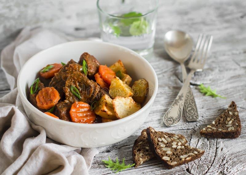 Goulash di manzo con le carote e le patate arrostite in una ciotola bianca fotografia stock