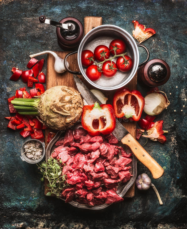 Goulash di manzo dei torelli con le verdure e gli ingredienti di cottura, preparazione sul tagliere e fondo rustico scuro fotografia stock libera da diritti