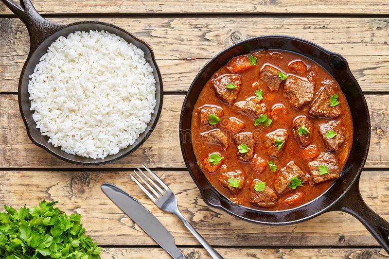 Goulash homemade Hungarian beef meat stew soup food cooked with spicy gravy sauce in cast iron pan meal served with rice. And chopped parsley on rustic wooden royalty free stock photos