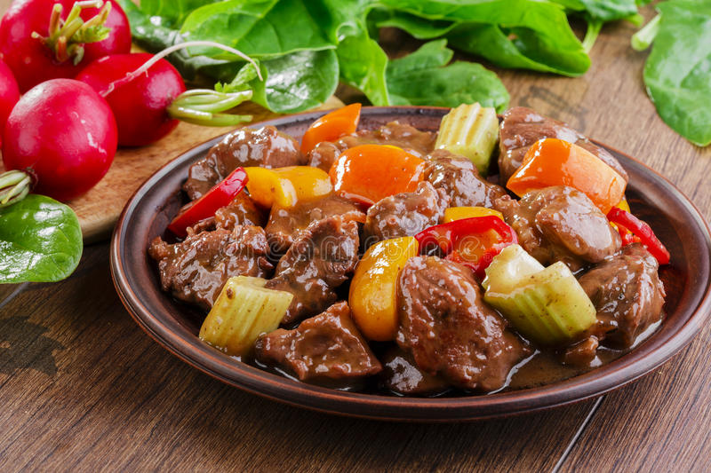 Goulash meat. With vegetables on the plate stock photos