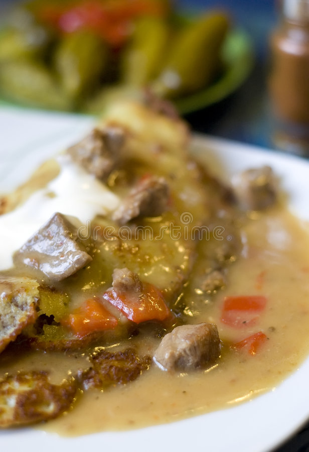 Goulash pie. A traditional Hungarian dish - a goulash pie or hungarian pancake. Bits of meat with sauce, pancake, cream, paprika, cucumber and chili. Spicy food stock photos
