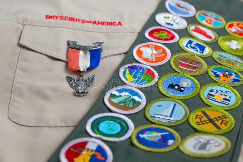 Goupille d'Eagle et ceinture d'insigne du mérite sur l'uniforme de scout de garçon image stock