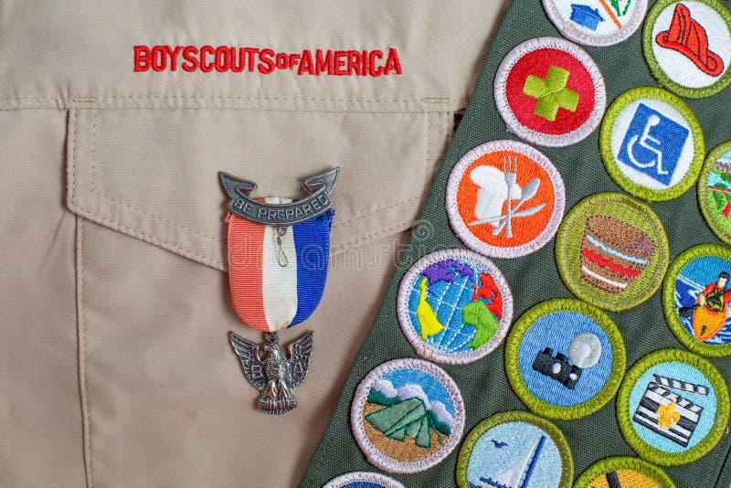 Goupille d'Eagle et ceinture d'insigne du mérite sur l'uniforme de scout de garçon photographie stock libre de droits