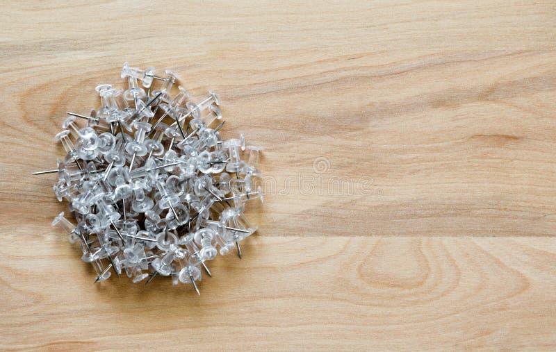 Goupilles en plastique de poussée sur un bureau avec l'espace de copie image libre de droits