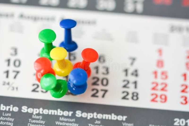 Goupilles multiples sur un calendrier suggérant le jour ou le programme occupé image libre de droits