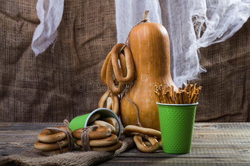 Gourd with cracknels and straws. Still life big gourd with bunches bind with string lying on sackcloth two disposable green cups with straws and hard oval royalty free stock photography