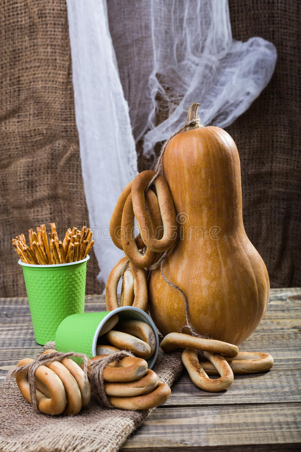Gourd with cracknels and straws. Still life closeup big gourd with bunches bind with string lying on sackcloth two disposable green cups with straws hard oval stock photos