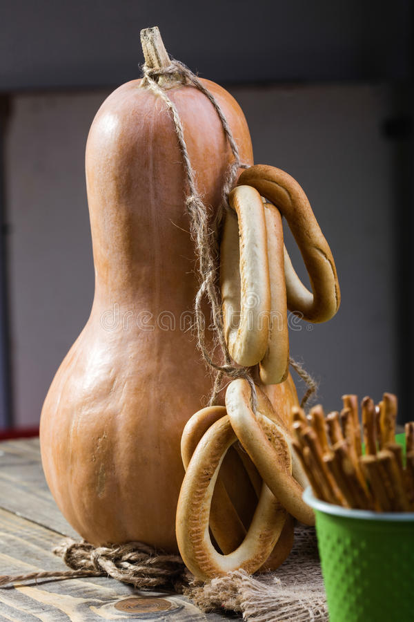 Gourd with cracknels and straws. Still life closeup one big gourd with bunches of hard oval cracknels bind with string and partial disposable green cup with royalty free stock image