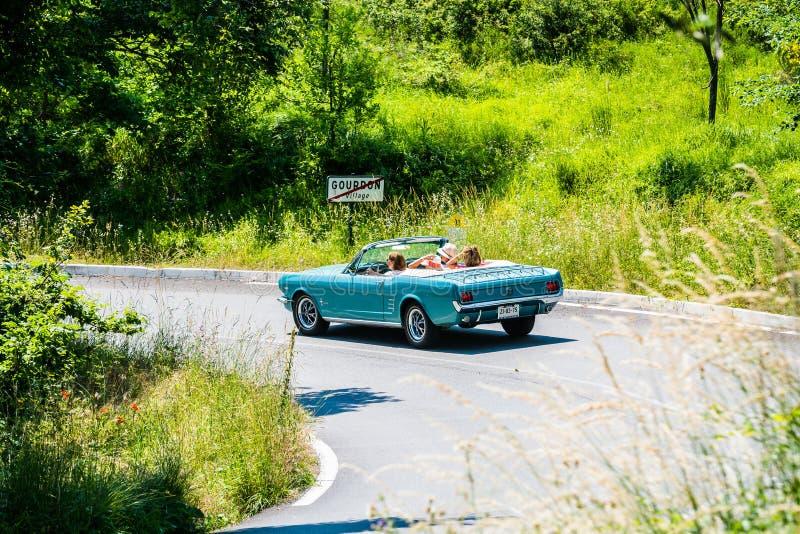 Gourdon, França - 20 de junho de 2018 Senhoras na viagem por estrada em Provence no mustang azul velho fotografia de stock