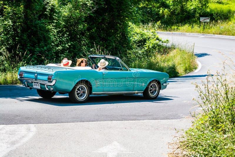 Gourdon, França - 20 de junho de 2018 Senhoras na viagem por estrada em Provence no mustang azul velho foto de stock