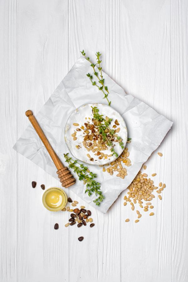 Gourmet appetizer of white brie cheese or camembert with thyme, nuts and honey dipper. Top view on gourmet appetizer of white brie cheese or camembert with stock photos