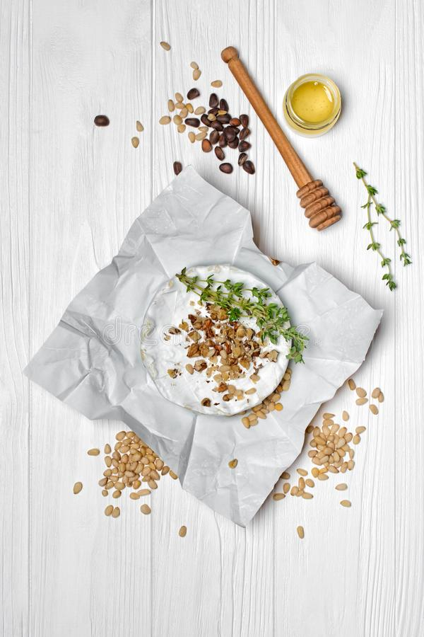 Gourmet appetizer of white brie cheese or camembert with thyme, nuts and honey dipper. Top view on gourmet appetizer of white brie cheese or camembert with royalty free stock photo