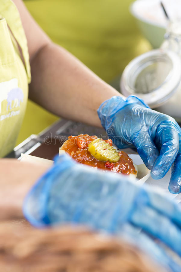 Gourmet burger at a food stall. Gourmet cheeseburger with relish and gherkin on top being prepared for customer royalty free stock photography