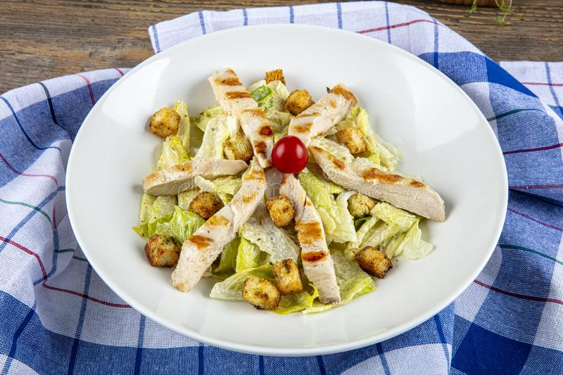 Gourmet caesar salad with grilled chicken croutons. Caesar salad with chicken, cherry tomatoes, lettuce royalty free stock photography