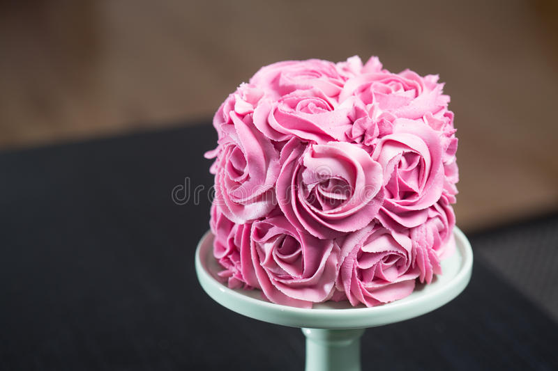 Gourmet cake decorated with pink roses. Gourmet cake for a wedding or birthday decorated with pink icing sugar roses covering the surface displayed on a stand royalty free stock images