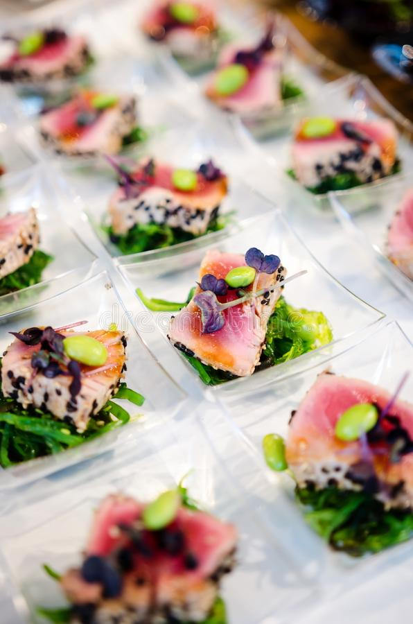 Gourmet catering food. Tuna steak with black sesame, wakame and edamame royalty free stock image