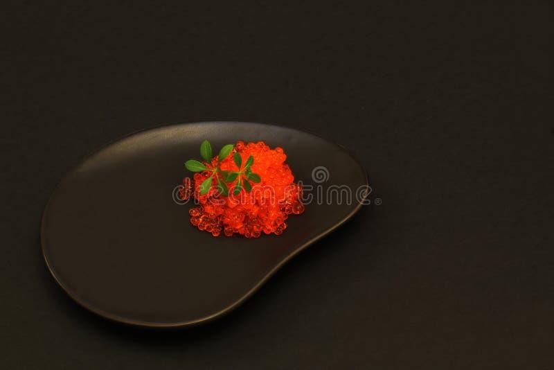 gourmet Caviale saporito salato di color salmone rosso con le giovani foglie verdi del crescione della lattuga sul piatto ceramic fotografie stock libere da diritti