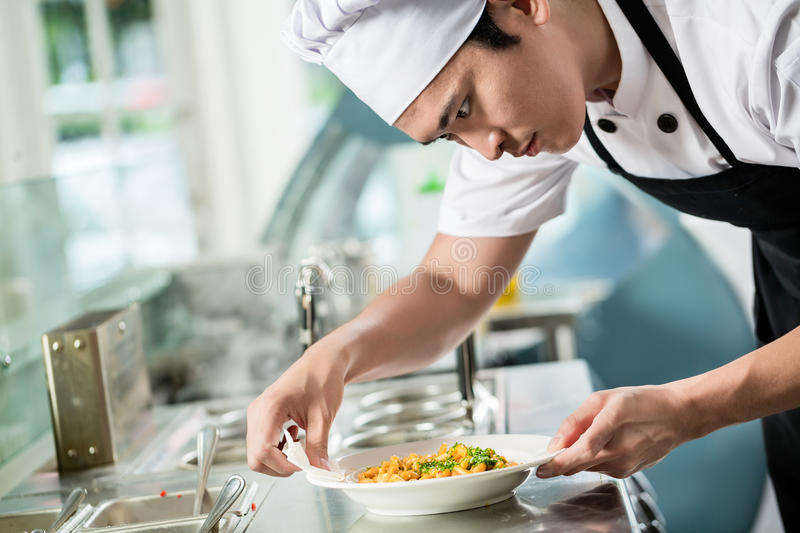 Gourmet chef plating up a dish of food. In an Asian restaurant carefully wiping the sides of the plate for spillage royalty free stock photos