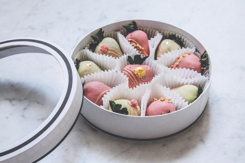 Gourmet chocolate covered strawberries in a round gift box stock image