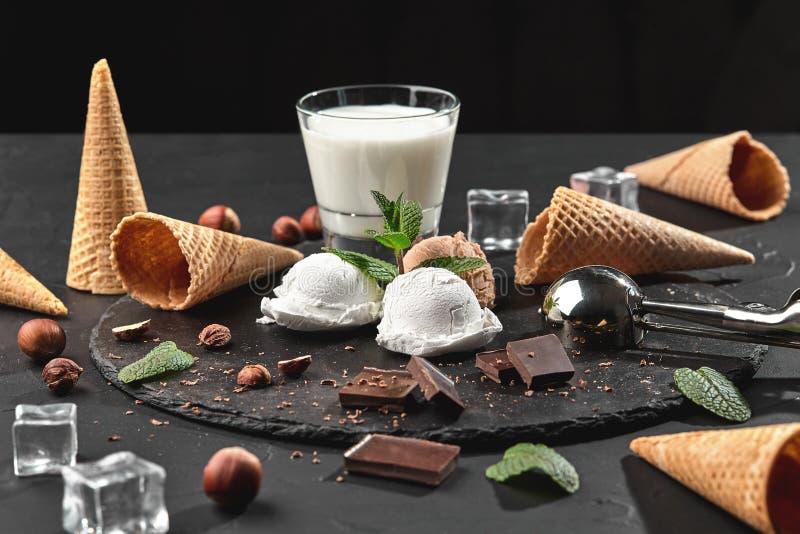 Gourmet- choklad och krämig glass tjänade som på en sten kritiserar över en svart bakgrund arkivbild