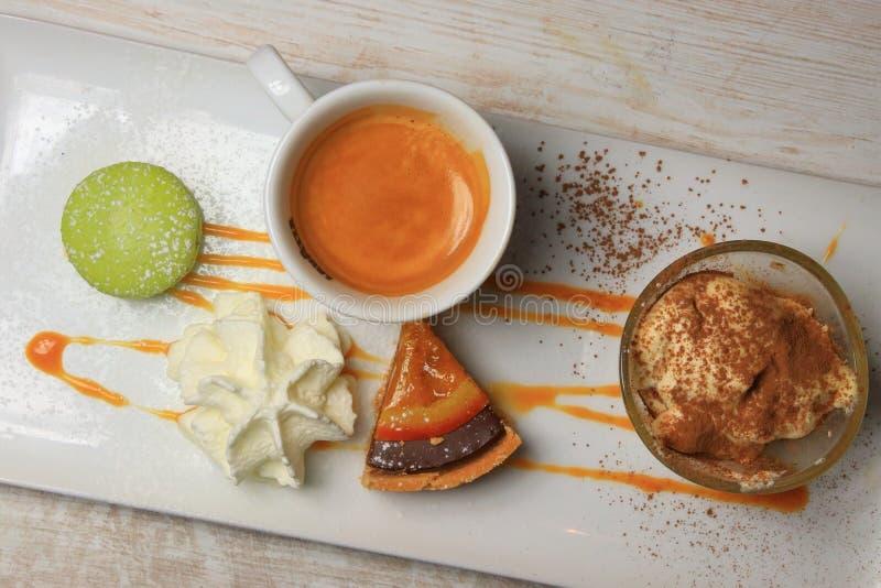 Gourmet coffee with macaron, cream and tart. Gourmet coffee with macaron, chantilly, cream and tart stock photography