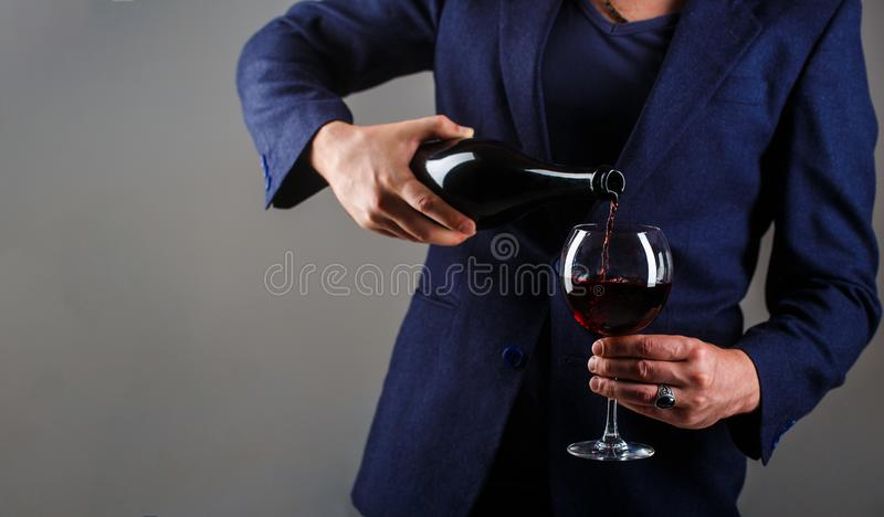 Gourmet drink bottle, red wine glass, sommelier, tasting. Waiter pouring red wine in a glass. Sommelier man, degustation. Winery, male winemaker. Red wine is royalty free stock photo