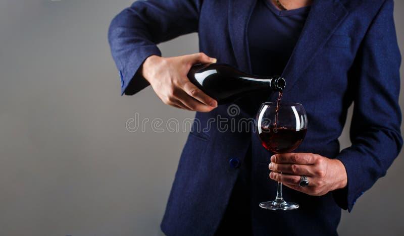 Gourmet- drinkflaska, rött vinexponeringsglas, sommelier, avsmakning Hällande rött vin för uppassare i ett exponeringsglas Sommel royaltyfri foto