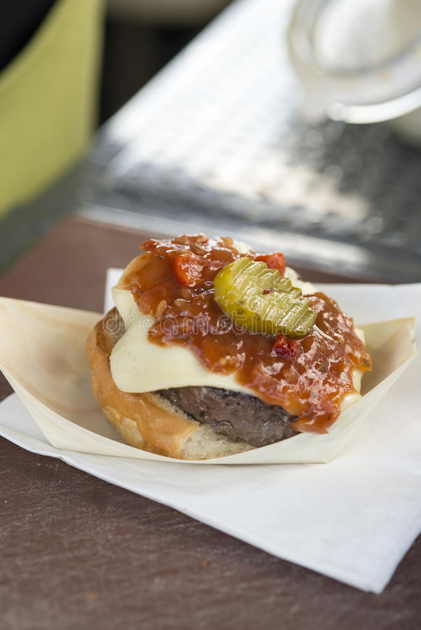 Gourmet fast food burger. Gourmet cheeseburger with relish and gherkin on top royalty free stock photos