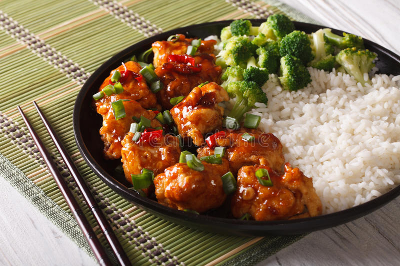 Gourmet Food: chickenTso's with rice, onions and broccoli close-. Gourmet Food: chicken general Tso's with rice, onions and broccoli close-up on a plate royalty free stock photo