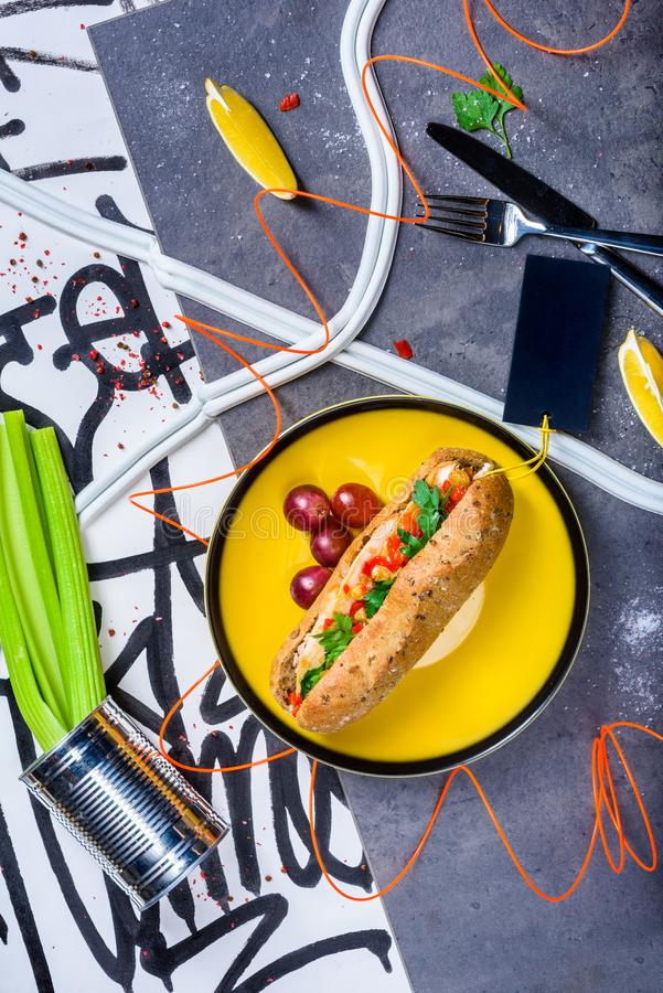 Gourmet grilled beef hot dog loaded with toppings.Top view. Gourmet grilled beef hot dog loaded with toppings. Grey marble background. Top view royalty free stock photo