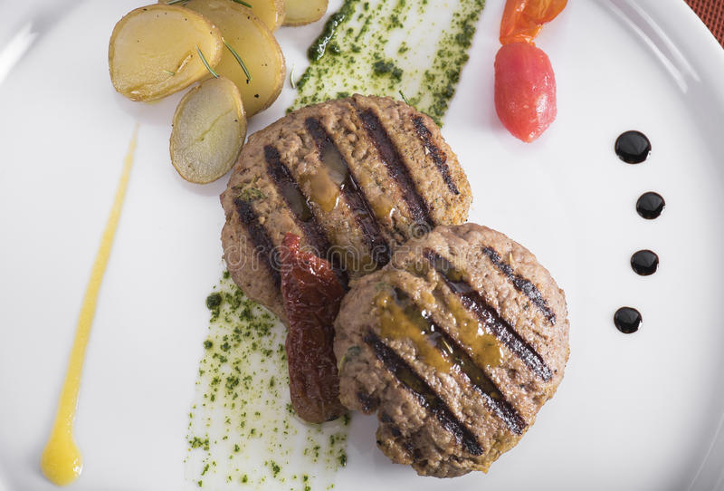 Gourmet Grilled beefburger with poached potatoes 4 stock photo