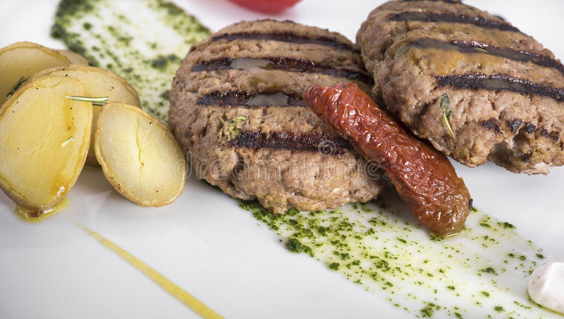 Gourmet Grilled beefburger with poached potatoes 1 stock photo