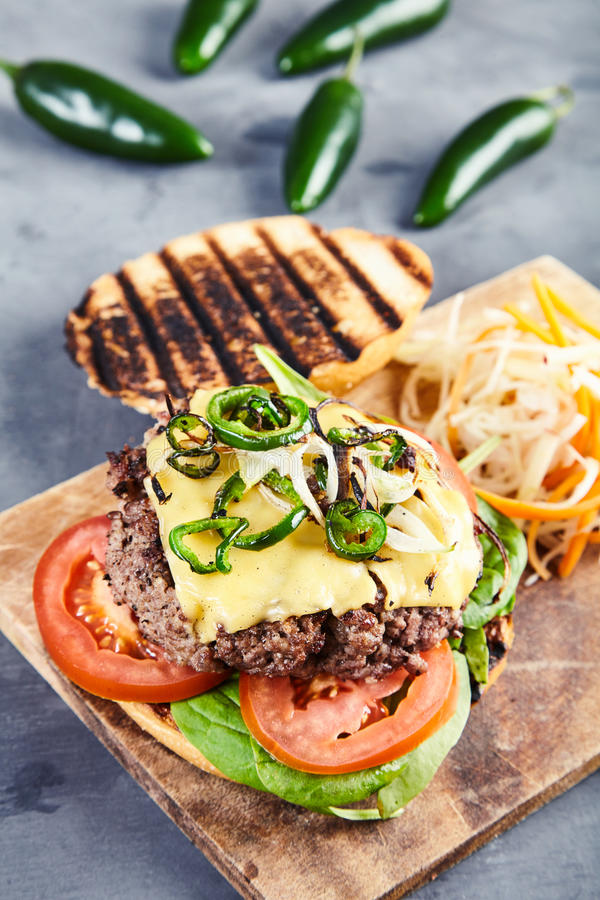 Gourmet- hamburgare med kryddiga jalapenos och spenat arkivfoton
