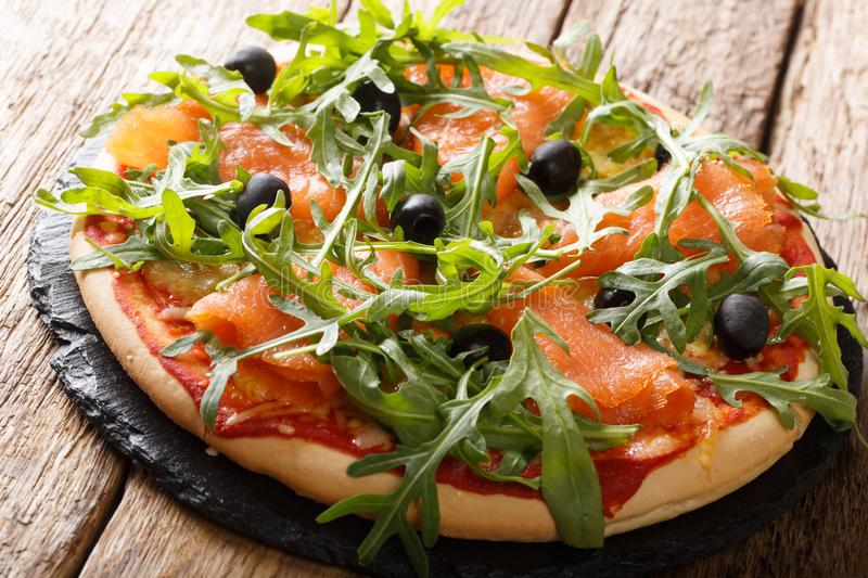 Gourmet Italian pizza with salmon, arugula, black olives and mozzarella cheese close-up. horizontal. Gourmet Italian pizza with salmon, arugula, black olives and royalty free stock image