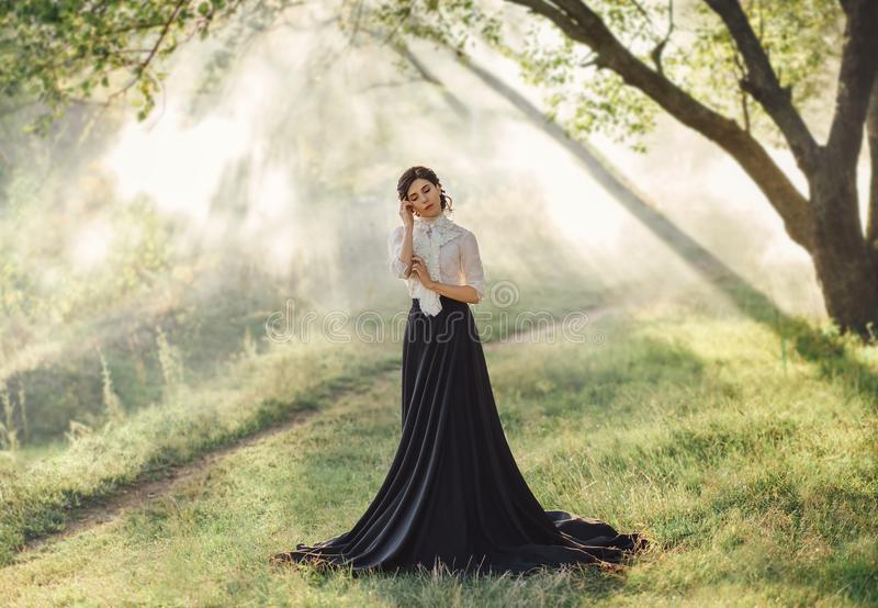 A girl in a vintage dress. Gourmet lady in a vintage dress with a frill. Walk in the fog. Artistic Photography stock images