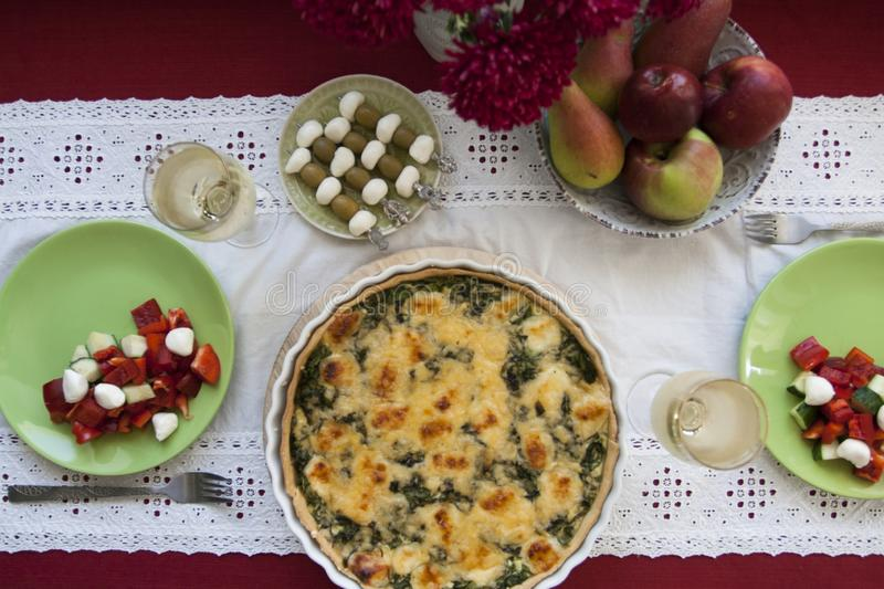 A gourmet lunch: spinach pie with cheese, a bowl of fruits, a salad and wine. A gourmet lunch for two: spinach pie with cheese, a bowl of pears and apples, a stock photo