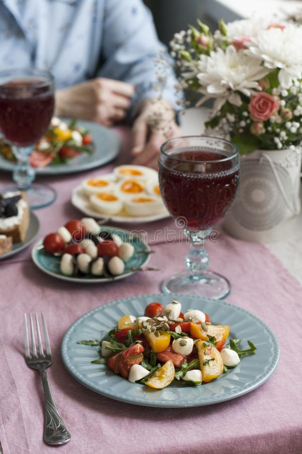 A gourmet lunch for two: salad, canapes, boiled eggs and wine. A gourmet lunch for two: two plates of tomato salad with mozzarella, aragula and pumpkin seeds stock photo
