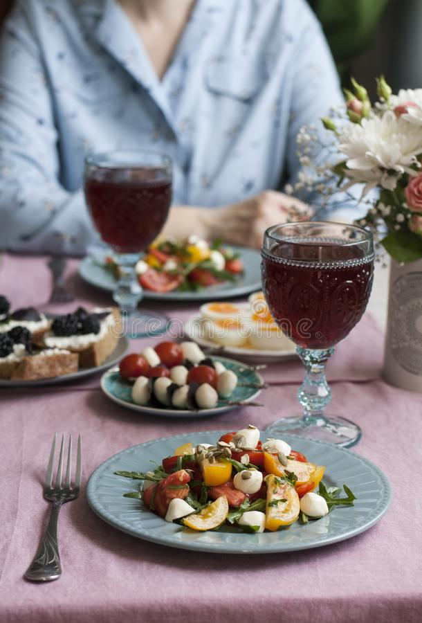 A gourmet lunch for two: salad, canapes, rye bread sandwiches, boiled eggs and wine. A gourmet lunch for two: two plates of tomato salad with mozzarella, aragula stock images