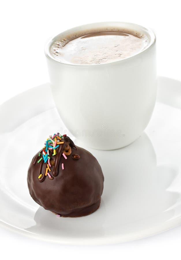 Gourmet- mörka chokladkonfektar och kopp kaffe på vit backgr arkivbild
