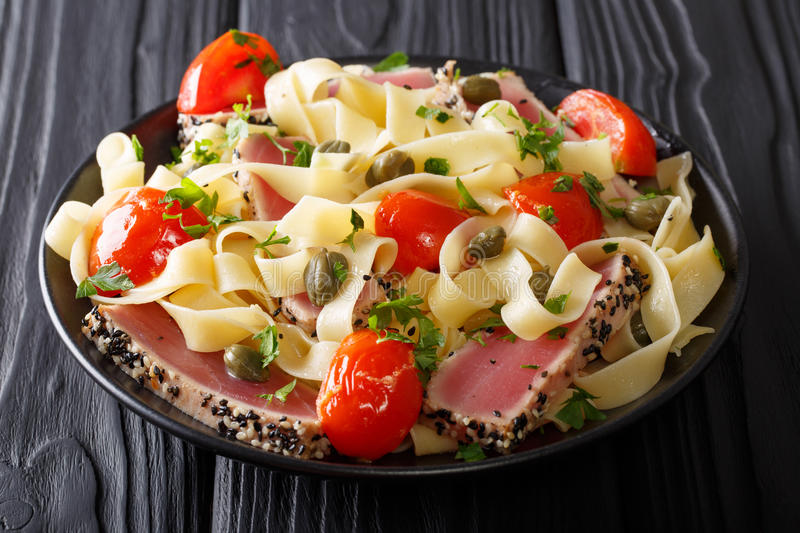Gourmet meal: Fettuccine pasta with fried tuna steak and vegetables closeup. horizontal royalty free stock photography