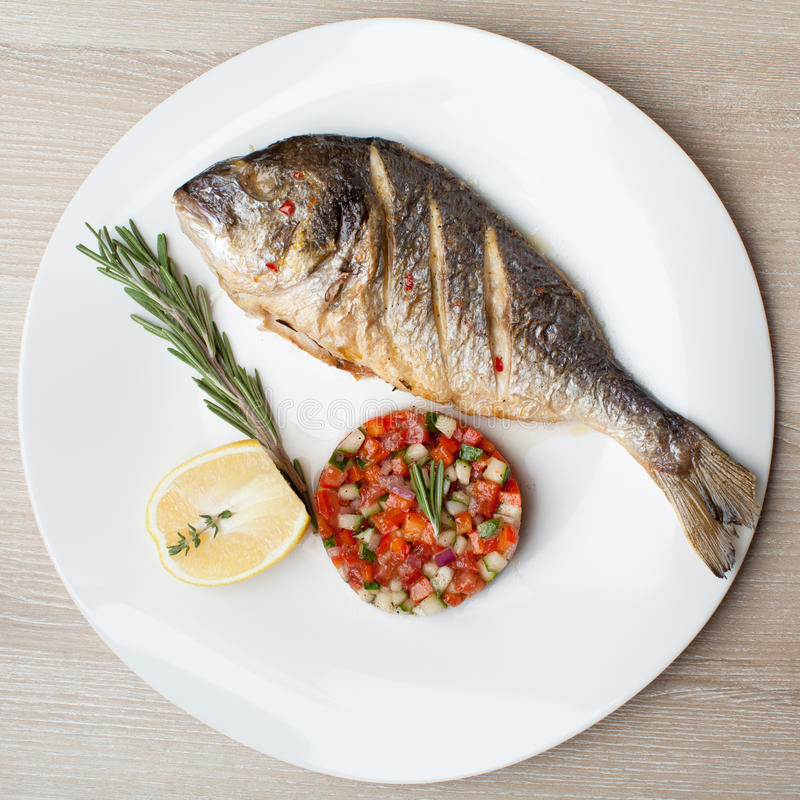 Gourmet Mediterranean seafood dish. Grilled fish gilthead with v stock photography