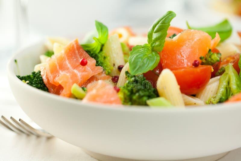 Gourmet pasta salad with smoked salmon. Pasta salad with salmon,broccoli and fresh herbs stock photo