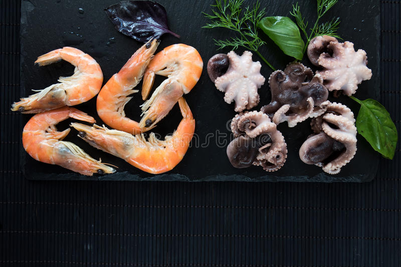 Gourmet pink shrimp and octopuses with herbs and spices. Preparing fresh seafood in the kitchen with gourmet pink shrimp and octopuses surrounded by fresh herbs stock image