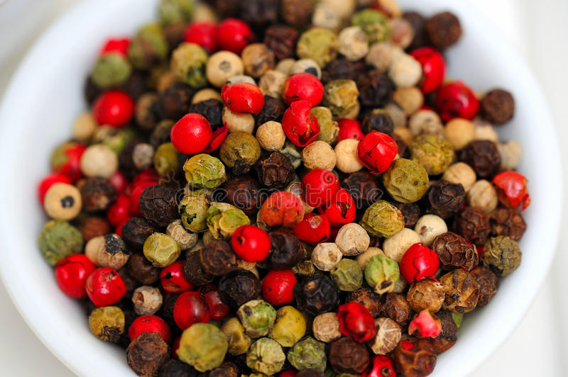 Gourmet Rainbow Peppercorns. Peppercorns in various colors of red, green and the familiar black peppercorn on white in a small bowl royalty free stock images