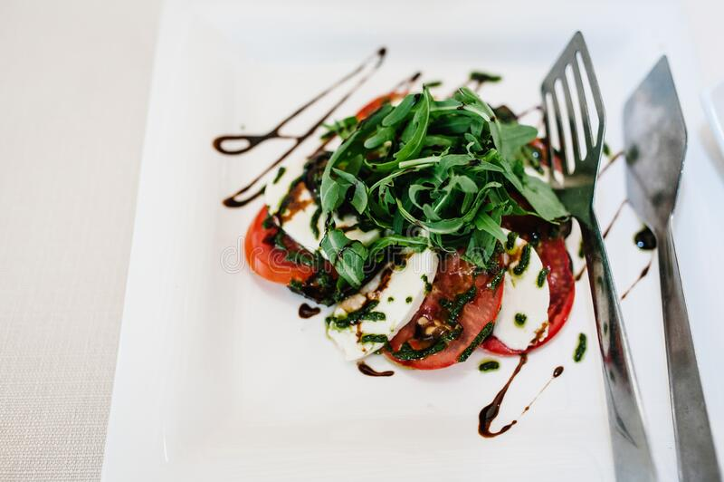 Gourmet salads isolated on white background. Tomato, Cheese, Brynza, Rukola..White plate on white table. Holiday food. Wedding day royalty free stock photos