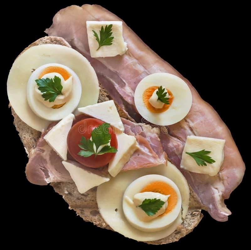 Gourmet- smörgås med baconskinkskivor Gammon Ham Cheese And Eggs Slices och tomaten som isoleras på svart bakgrund royaltyfri fotografi