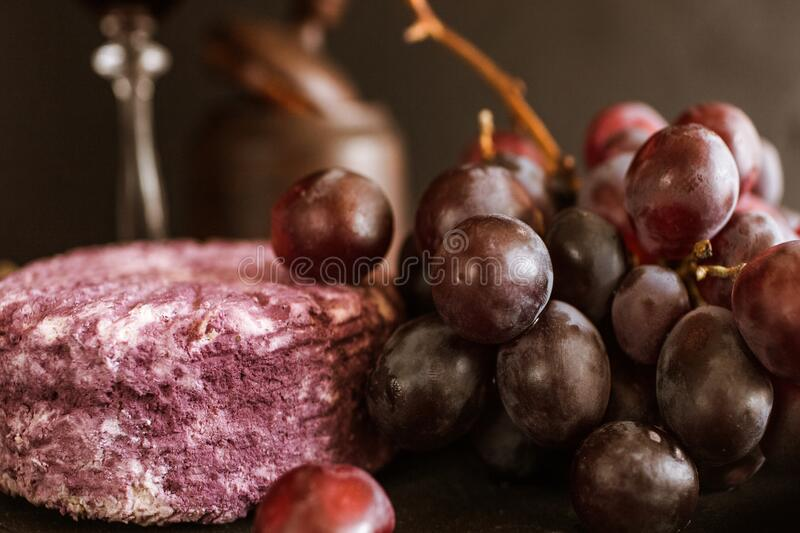 Gourmet snacks food composition grape cheese. Gourmet snacks. Food composition. Grape cluster purple cheese arrangement stock images