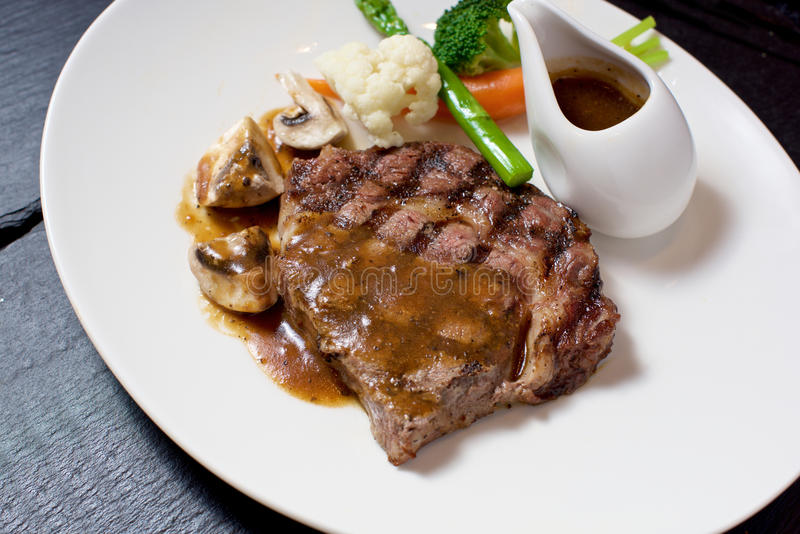 Gourmet Steak dish. On white plate on slate royalty free stock photos